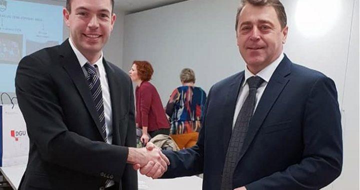 Slika prikazuje fotografiju glavnog ravnatelja Državne geodetske uprave i predsjednika komisije za standardizaciju zemljopisnih imena Republike Slovenije.